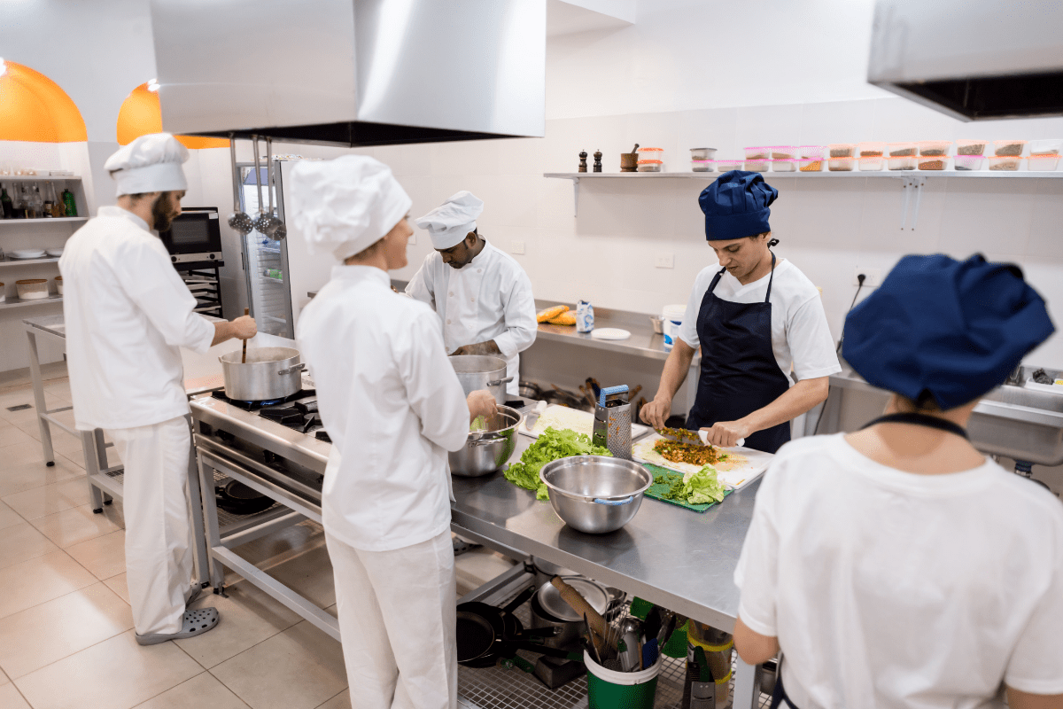 Chefs in commercial kitchen standing at a stainless table doing food prep