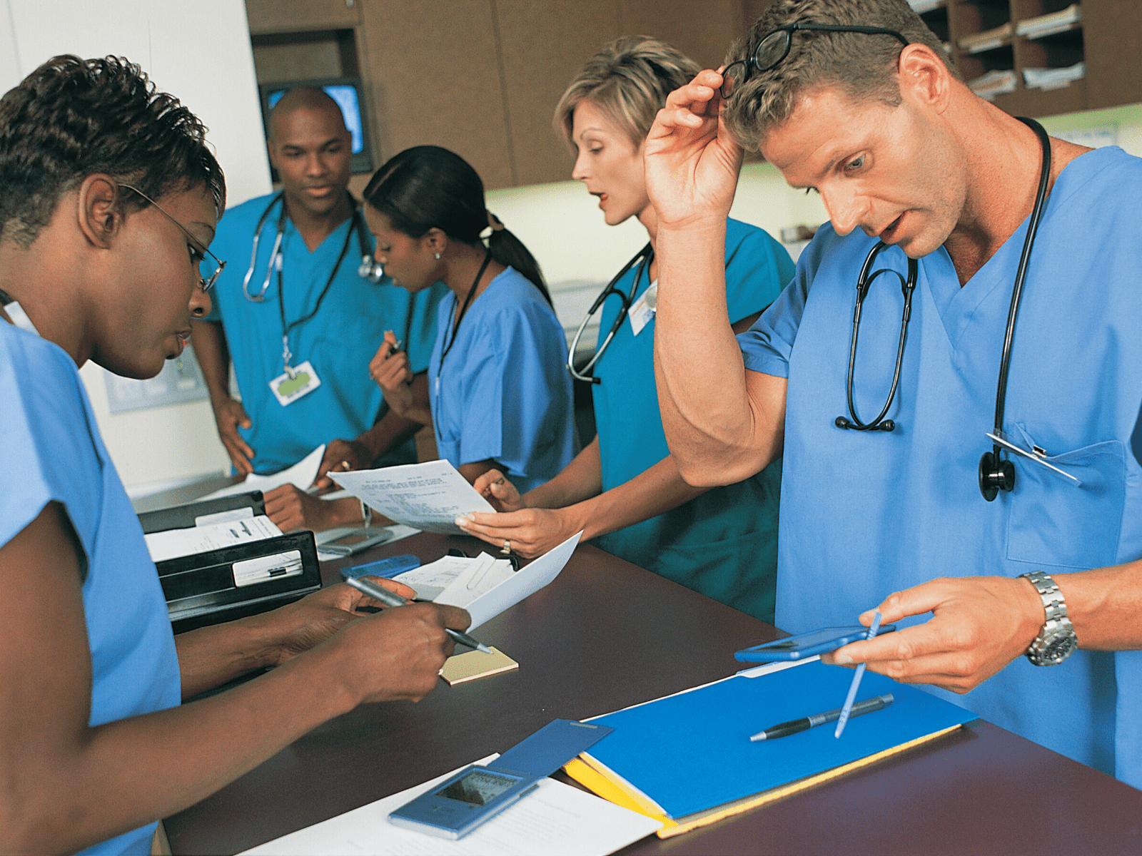 Five doctors in blue scrubs standing around a table with paperwork